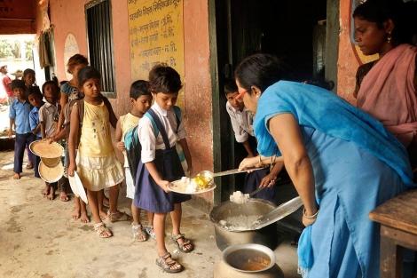 Varios niños sin recursos reciben alimento en la escuela.| Afp