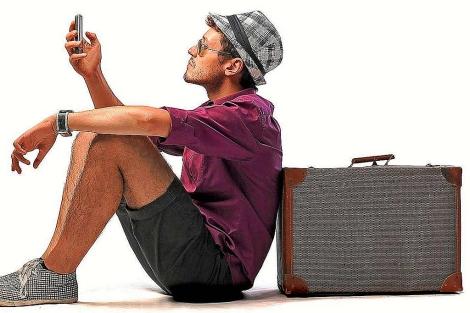 Un turista consulta su móvil apoyado en la maleta.| EM