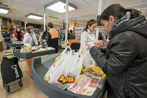 Una mujer mete la compra en bolsas en la caja del supermercado