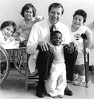 Foto en blanco y negro de un doctor rodeado de ñiños y adultos con problemas de hipocrecimiento