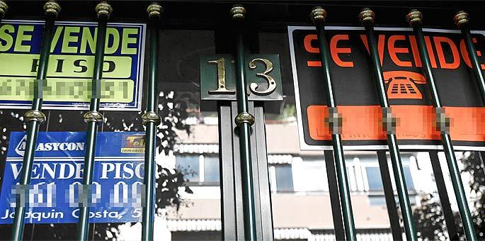 Varios carteles anuncian la venta de pisos en el mismo portal de un edificio de Madrid.