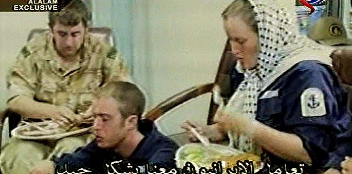 La única mujer apresada (d) come junto a dos de sus compañeros, en una imagen emitida por la televisión iraní.