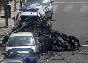 Varios bomberos extinguen las llamas en un coche afectado por la explosión. (Foto: AFP)
