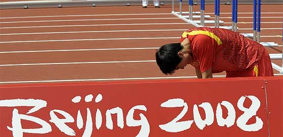 Liu Xiang, roto por el dolor antes de su serie. (Foto: AP)