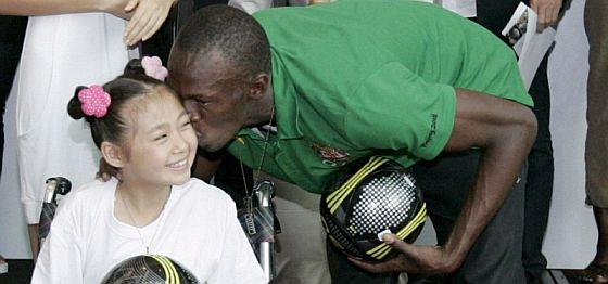 Bolt besa a una niña que perdió una pierna en el terremoto de la provinvia china de Sichuan. (Foto: EFE)
