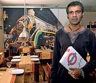 Próxima estación: La India. El propietario del nuevo establecimiento, Nadeem, posa en el comedor, decorado con motivos ferroviarios. (Foto: Carlos Barajas)