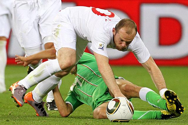 Rooney cae sobre un defensor argelino. (Efe)