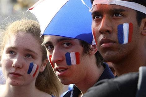 Tres aficionados franceses, apesasumbrados tras la eliminación. (AP)