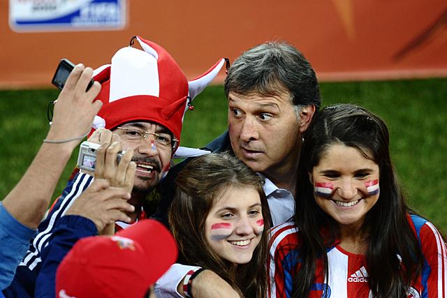 Gerardo Martino, rodeado de fans tras la clasificación de Paraguay para octavos de final. (Afp)