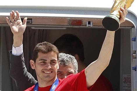 Íker Casillas, con el trofeo, a la salida del avión. (EFE)