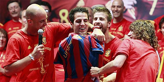 Reina, Piqué y Puyol visten a Cesc de azulgrana. | Reuters