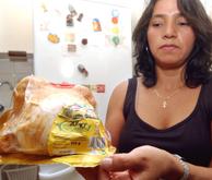 Sonia, una ciudadana ecuatoriana y residente en Murcia muestra uno de los pollos en mal estado. (Foto: EFE)