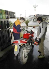 Un trabajador de una gasolinera llena el depósito de una moto. (Foto: DAVID DE HARO).