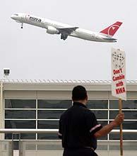 Un trabajador de Noertwest protesta en el aeropuerto de Detroit ante un aparato de su compañia. (Foto: REUTERS)