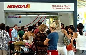 Varios pasajeros, frente a un mostrador de atención al cliente de Iberia, en Barajas (Madrid). (Foto: EFE)