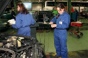 Mujeres en un taller pasando la ITV a un vehículo. (Chema Tejada)