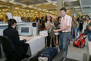 Viajeros con ensaimadas en los mostradores de facturación del aeropuerto de Mallorca. (Foto: Jordi Avellà)