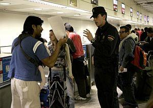 Un pasajero afectado habla acaloradamente con un policía. (Foto: EFE)