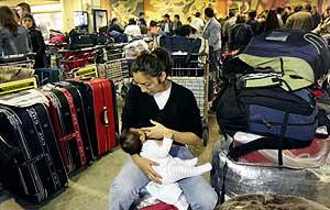 Una pasajera de Air Madrid da el pecho a su bebé en el aeropuerto de Barajas. (Foto: AP)