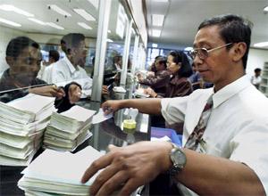 Un empleado del Banco de Indonesia valida varios fajos de cheques. (REUTER)