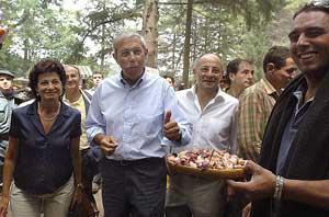 El presidente de la Xunta de Galicia, Emilio Pérez Touriño, acompañado de su esposa y del acalde de Ourense, Francisco Rodríguez , prueba una ración de pulpo. (Foto: EFE)