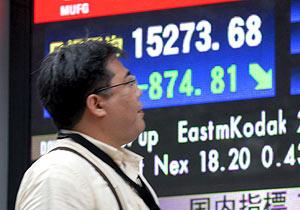 Un hombre mira el panel electrónico con las cifras del cierre de la Bolsa de Tokio. (Foto: EFE)