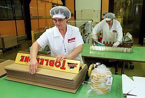 Una empleada embalando una tableta gigante de Toblerone en la fábrica que tiene la empresa en Berna, Suiza. (FOTO: EFE)