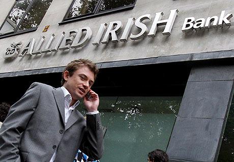 Un viandante pasa por delante del banco irlandés Allied Irish. (EFE)