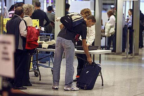 Miembros del personal del aeropuerto de Barajas ayudan a los viajeros a seguir las normas de seguridad para el equipaje de mano de la Unión Europea. (Foto: EL MUNDO)