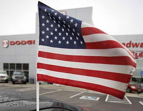 Una bandera de EEUU ondea delante de un concesionario de 'Dodge' en Denver, Colorado. | Foto: AP