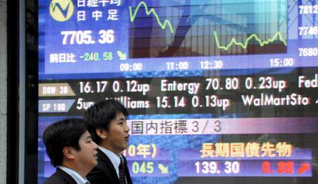 Ejecutivos japoneses pasan junto a un panel electrónico con información bursátil del centro de Tokio.|Efe