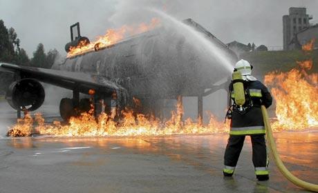 Un bombero apaga las llamas de un avión durante la realización de un simulacro| AENA