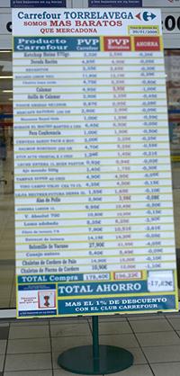 Un panel a la entrada de un Carrefour con el lema: 'Somos más baratos que Mercadona'