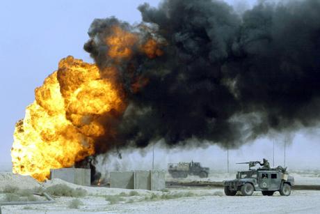 Un convoy de Marines de EEUU pasa junto a un pozo de petróleo incendiado en la region de al-Ratka, al sur de Irak, en el inicio de la ofensiva estadounidense sobre Irak, en marzo de 2003.   Odd Andersen