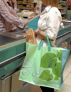 Una mujer con una bolsa reutilizable en un supermercado Carrefour. | Marta Arias