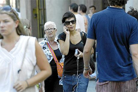 Una mujer utiliza su teléfono móvil en plena calle. | Doménec Umbert