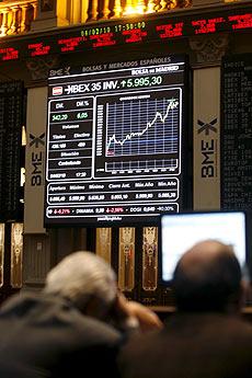 Inversores miran el desplome en las pantallas de Bolsa en la sede del parqué madrileño. | Víctor Larena (Efe)