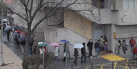 Varios jóvenes forman cola frente a una oficina de empleo en Madrid. | Óscar Monzón