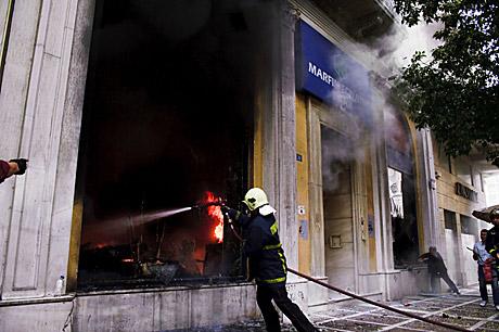 Un bombero intenta apagar las llamas de la sucursal incendiada. | AP