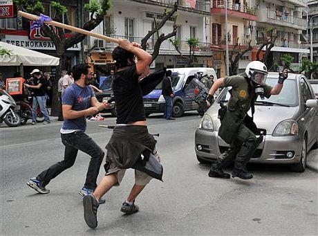 Un policía antidisturbios huye de los manifestantes.   AP.