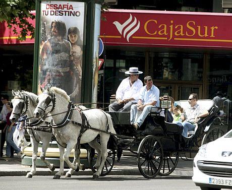 Varios turistas pasean en un coche de caballos ante una de la sede central de Cajasur en Córdoba. | Efe
