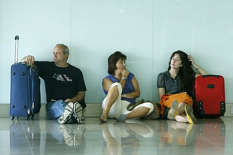 Varios pasajeros esperan sentados en la Terminal 1 del aeropuerto de El Prat. | Efe