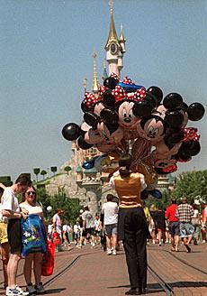 Una empleada del parque vendiendo globos de Disney.   AP