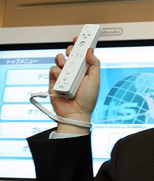 Satoru Iwata, presidente de Nintendo, sujeta el mando de la Wii con la famosa correa. (Foto: AP)