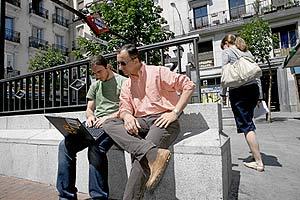 El director de la revista Zero (d) y el responsable de Fon España (i) navegan por Internet en la Plaza de Chueca. (Foto: Antonio M. Xoubanova)