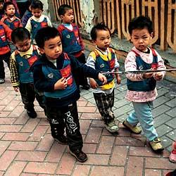 Los padres de ciudades como Kunming, donde la cadena de secuestros de hijos varones está fuera de control, llevan a sus hijos al colegio encadenados. / RICHARD JONES