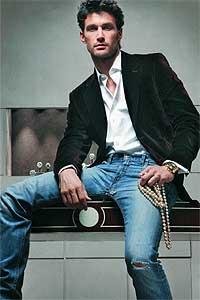 """Americana, 475 e, y camisa, 150 e, de CH de Carolina Herrera. Vaqueros, 90 e, de Pepe Jeans. Reloj de Franck Muller, 29.714 e, y collar de perlas """"golden"""", 119.500 e, de Suárez."""