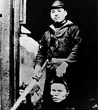 EL SAMURAI. Un soldado japonés posa orgulloso con la cabeza de un chino al que acaba de decapitar / CORBIS
