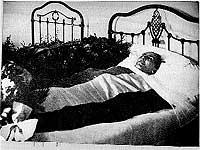 Yacente. Al día siguiente de su muerte, acaecida el 22 de febrero de 1939 en Collioure (Francia), Antonio Machado es envuelto, sobre la cama, en una bandera republicana que ha cosido una vecina