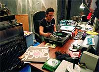 """El """"dj"""" escucha varias docenas de discos que acaba de recibir."""